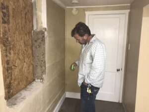 inspecting crack in wall