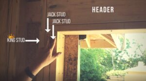 Man pointing to a kind stud and jack stud that make up a header above a walkway in a house