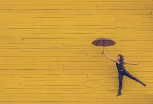 woman with umbrella yellow wall